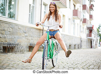 Bicycle fun - Portrait of happy young woman on bicycle