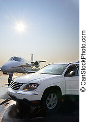 Private Jet and Car Rental - A white SUV is parked on a wet...