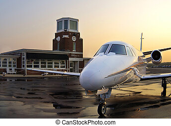 Private Jet at Sunrise - A white private jet parked on a wet...