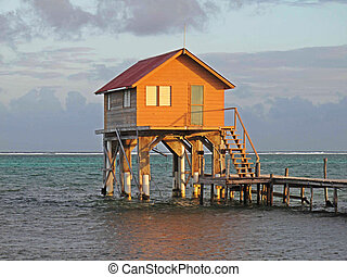 Hut above the water Sunset - Colorful hut along the shore at...