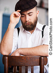 Thinking about... Handsome young bearded men sitting on the chair and holding a his hat