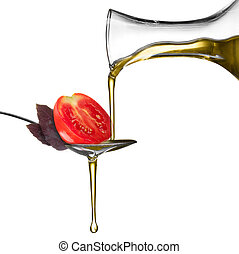 Pouring oil on spoon with basil and tomato isolated on white