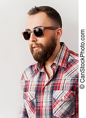 Cool and trendy. Side view of handsome young man in sunglasses looking away