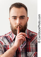 Keep silence. Portrait of handsome young bearded man making...
