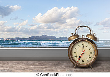View of summer sea under blue sky from window with alarm clock