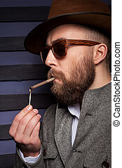 Taking a break to smoke. Handsome young man in sunglasses lights a cigarette