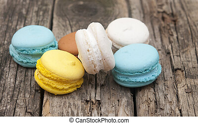 Colorful macaroons, delicious French pastries, stacked on table.