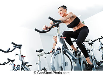 woman veloargometer gim fitness - Young athletic female...