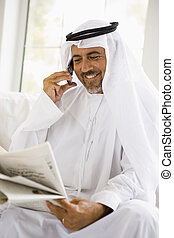 A Middle Eastern man talking on a mobile phone while reading...