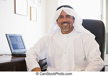 A Middle Eastern man sitting in front of a computer at home
