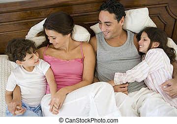 A Middle Eastern family lying on a bed