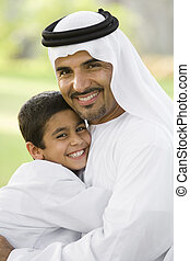 A Middle Eastern man and his son sitting in a park