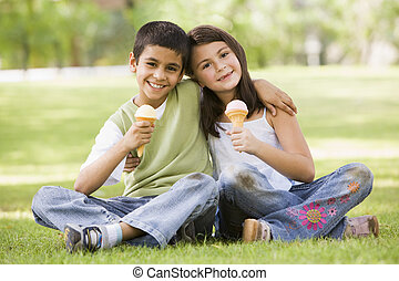 Two children eating ice cream in park - Two children eating...