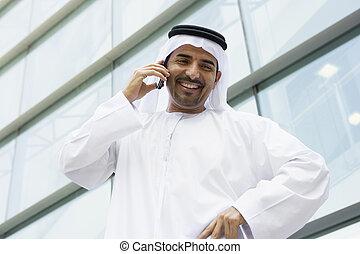 A Middle Eastern businessman talking on the phone outside an...