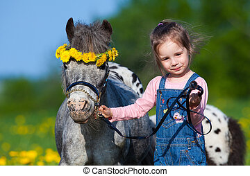 Child and small horse in field - Child with small horse...