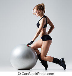 Fitness with gym ball - Athletic woman makes exercises on a...
