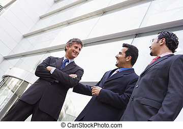 Group of businessmen outside office building - Group of...
