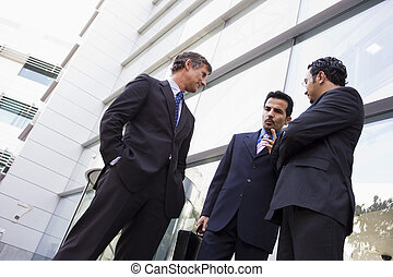 Group of businessmen talking outside office