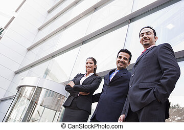 Group of business people outside office building - Group of...