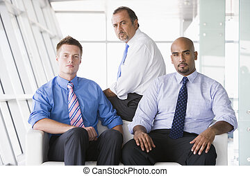 Group of businessmen sitting in lobby - Group of businessmen...