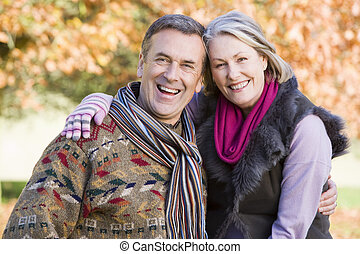 Affectionate senior couple on autumn walk with trees in...