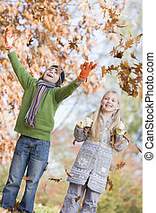 Two children throwing leaves in the air - Two children...