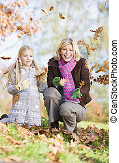 Mother and daughter throwing leaves in the air