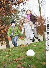 Mother and children playing football in garden