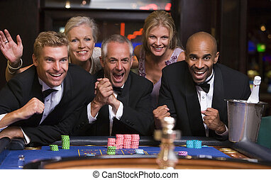 Group of friends celebrating win at roulette table in casino