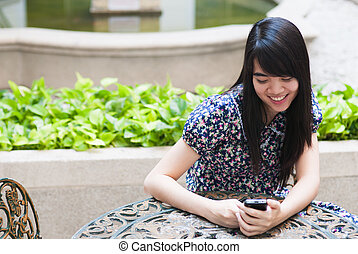 Young happy asian woman is calling with a mobile phone