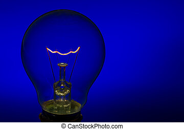 Glass light bulb with burning filament upright with bright...