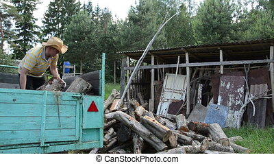 man unload wood woodshed - strong worker man unload tree...