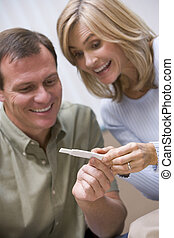 Couple looking at home pregnancy test - Couple looking at...