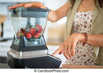 Health conscious woman using a blender