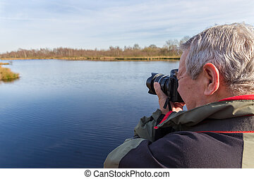 Senior man taking photos standing at a lake