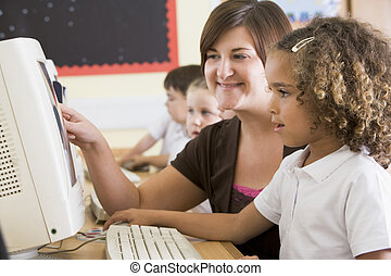 A girl and her teacher working on a computer at primary...