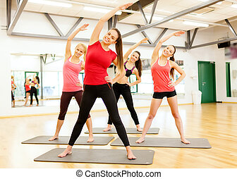 group of smiling women stretching in the gym - fitness,...