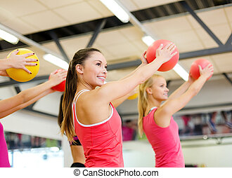 group of people working out with stability balls - fitness,...