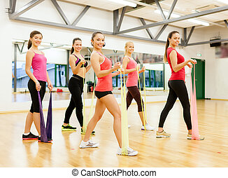 group of people working out with rubber bands - fitness,...