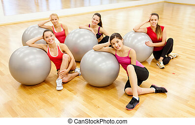 smiling people working out in pilates class - fitness,...