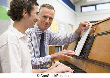 Teacher with schoolboy playing piano in music class