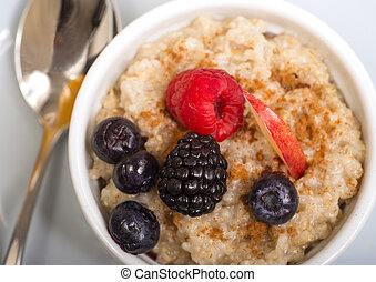 Bowl of steel cut oats served with fresh fruit and honey -...