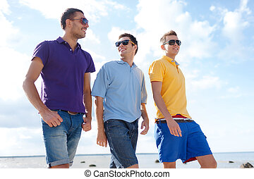 group of male friends walking on the beach - summer,...