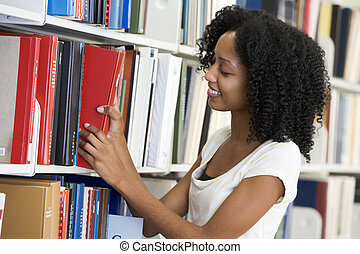University student working in library - Female university...