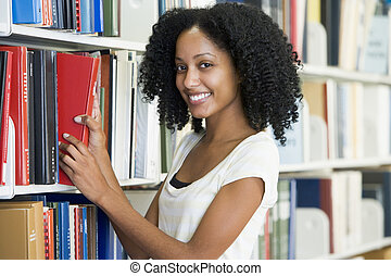 University student selecting book in library - Female...
