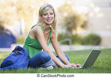 University student using laptop outside - Female university...