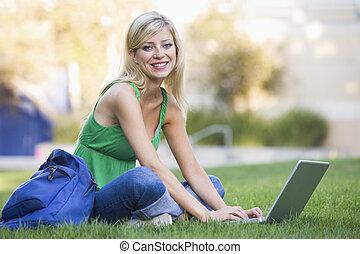 University student using laptop outside - Female university...