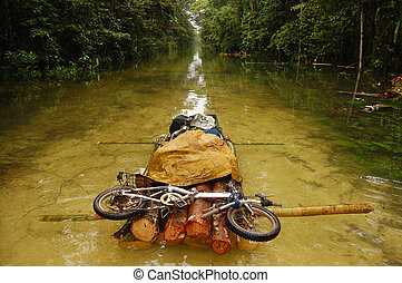 Folding bycicle at raft flooded gravel road, Papua New...