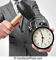 broking an alarm clock - a man wearing a suit broking an...