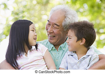 Grandfather laughing with grandchildren